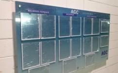 Quadro de avisos em vidro fixado na parede com prolongadores e personalização em vinil adesivo com impressão digital e bolsas em acrílico